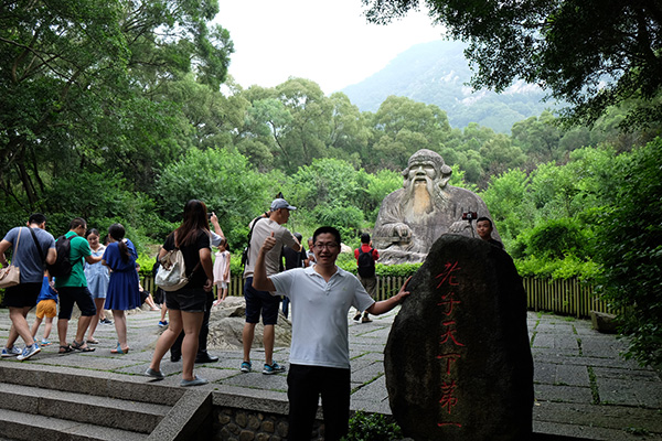 People posing with the stone statue of Laozi at the foot of Qingyuan Mountain.