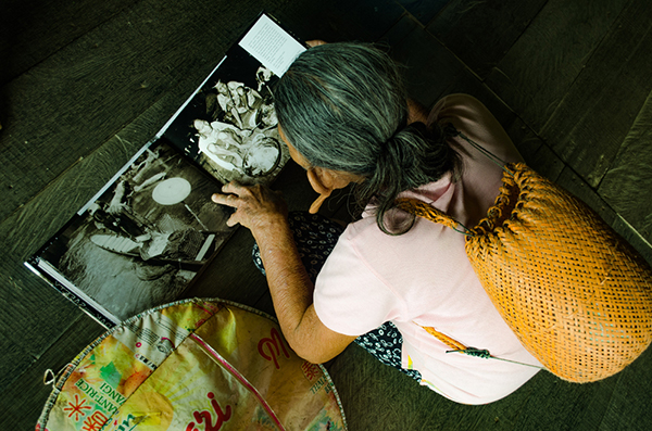 A woman studies photos in a book in Long Luyang, Tinjar. – Photos by C Horn and R Riman