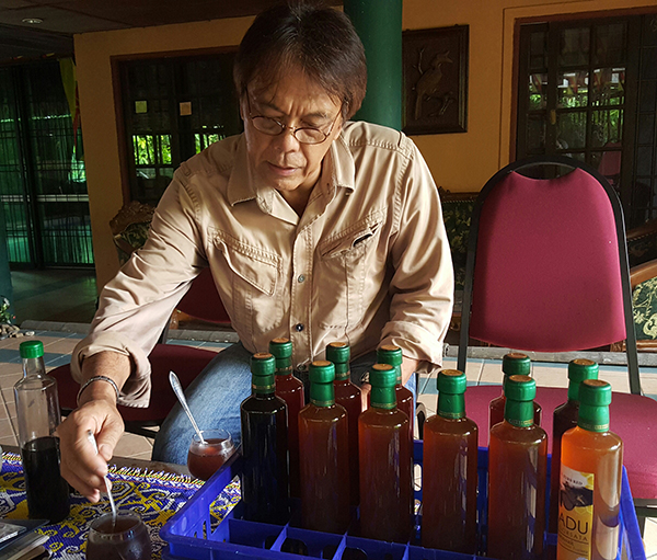 Elli stirs kelulut bee honey in a glass of plain water.