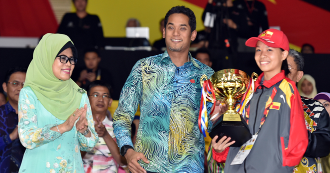 Khairy presents the Best Female Athlete award to Carmen Lim of Selangor. At left is Fatimah.