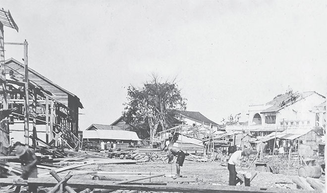 The captured scene shows the aft ermath of the 'Great Fire of Sibu' in 1928. All features as seen on this photo are gone, except for the tree at the centre and the concrete block on the right. The raintree in front of Tua Pek Kong Temple is now the oldest tree in Sibu Central Business District. Tua Pek Kong Temple was also rebuilt.