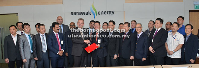 Sjøtveit (front, fifth left) exchanges the signed documents with Sinohydro Corporation executive vice president Liu Wei, as others look on.