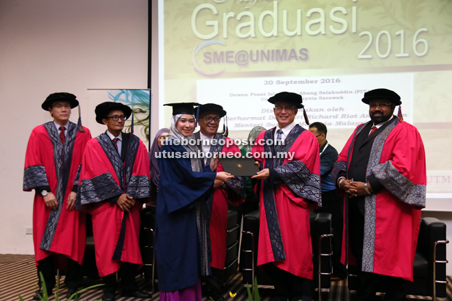 Riot presents a certificate to a graduate. From right are Vignaesvaran, Kadim, Affendy and Kopli.