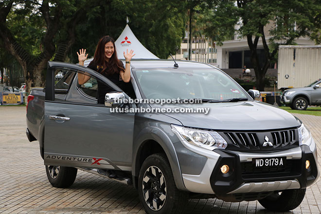 Leona waving to the crowd after unveiling the capabilities of the new Mitsubishi Triton VGT Adventure X.