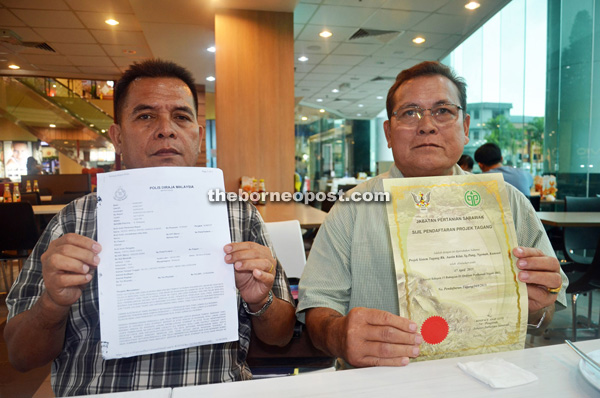 Entili (left) shows the police report while Pengiran is showing the certificate for the association's Tagang system at Sungai Pang in Ulu Ngemah.