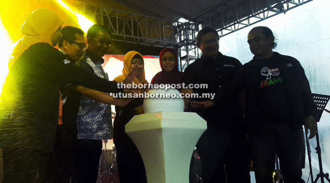 Karim (third left) and Salmah (fourth right) together with RTM senior officers place their palms on the globe in a symbolic gesture to declare open the Sehati @RTM Berambeh.