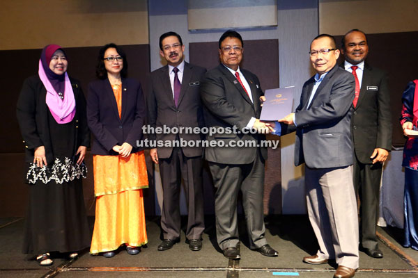 Zainal (fourth left) hands over a certification to a recipient. — Photo by Muhammad Rais Sanusi