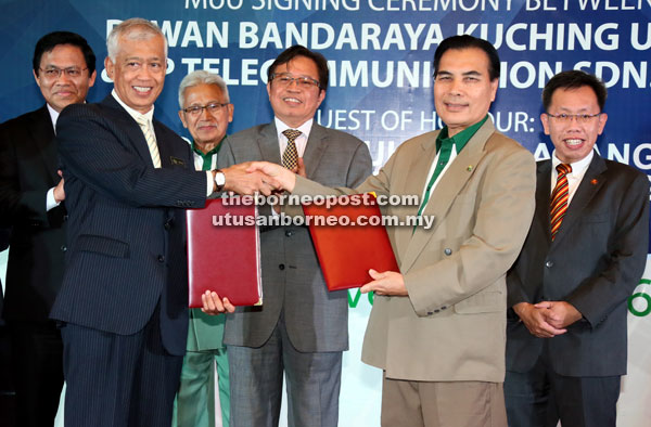 Abang Johari (third right) witnesses the exchange of documents between Abang Jemat (second right) representing PPTelecom and Abang Abdul Wahap representing DBKU. Looking on are Dr Sim (right), Abang Talhata (third left) and Dr Abdul Rahman. — Photo by Kong Jun Liong