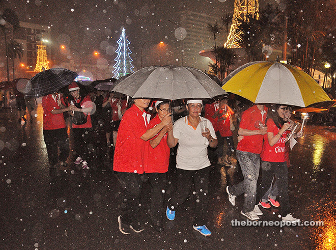GLORY TO GOD: More than 10,000 people braved strong winds and downpour to take part in the annual Christmas parade in Sibu last night. It started to rain about 10 minutes after the start of the spectacle, which was hosted by St. John's Church under Venerable Archdeacon Jamal Senada. — Photo by Othman Ishak.