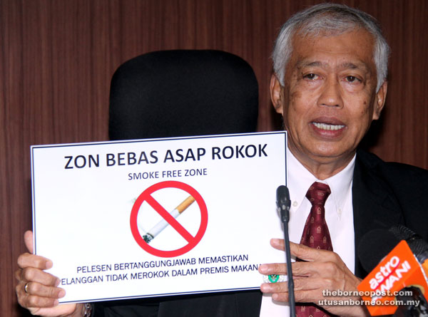Abang Wahap holding the no-smoking zone notice to be displayed at all coffee shops within DBKU area come Jan 1 next year.