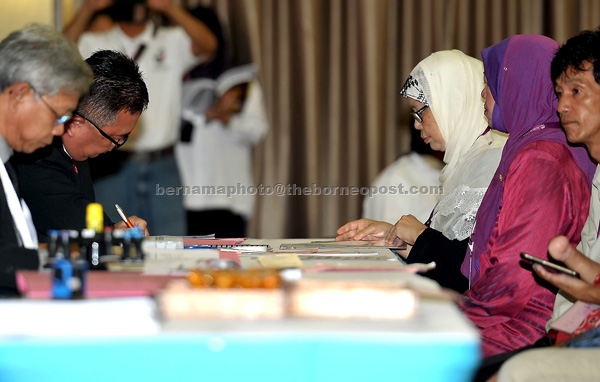 Jamilah  (second right)  submits the candidate's form at the nomination centre in Dewan Masyarakat Lundu. — Bernama photo