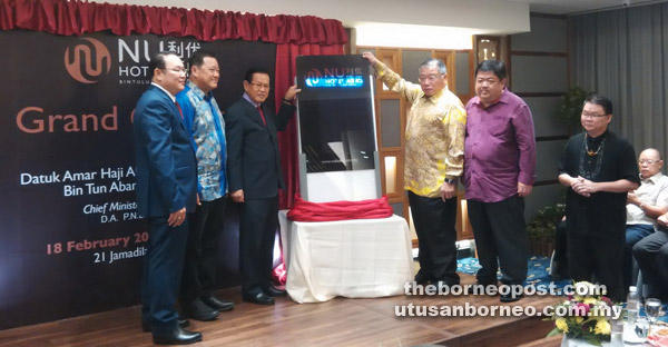 Lee and Tiong (third and fourth left, respectively) jointly unveil the banner board to mark the grand opening of Nu Hotel Bintulu.