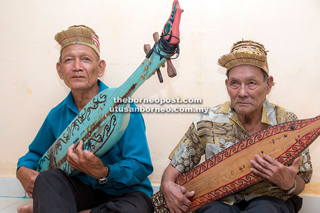 Two men playing Sape a traditional music instrument of Orang Ulu people. — Photos by Wilson Chiam