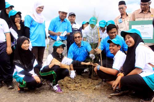 FOREST REHABILITATION: (From third left, squatting) Len Talif and Dr Rahman with school children participating in a tree planting activity organised in conjunction with World Wetlands Day 2013. — Photos by Jeffery Mostapa.