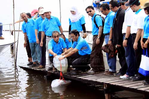 REPLENISHING: Len Talif and Dr Rahman (right) releasing fish fry into Sg Lemidin.
