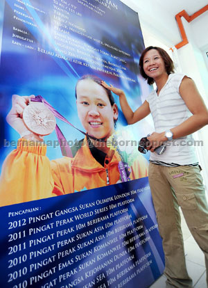 LATEST ACCOLADE: Pandelela touches a poster of herself during her visit at the Sarawak Aquatic Centre in Kuching, in this Aug 28, 2012 file photo. — Bernama photo