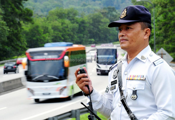 SMOOTH TRAFFIC FLOW : A police traffic officer monitoring traffic movement along the East Coast Highway near Bentong Toll Plaza. – Bernama photo
