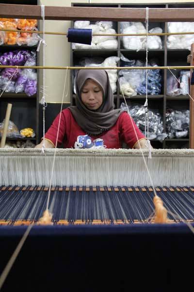 TOUGH JOB: A weaver is almost dwarfed by the large loom she works on. Learning to weave songket is not for the faint-hearted. In addition to its physical demands, it requires intense concentration, excellent attention to detail, a head for numbers, and copious amounts of patience and perseverance.
