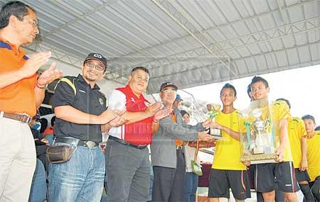 TAHNIAH: Mohidin (empat kiri) menyampaikan hadiah kepada para pemain SMK Sebauh sambil disaksikan Wan Ibrahim (kiri), Awg Alauddin dan Duke.