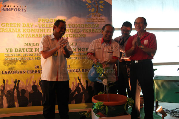 MORE GREENERY: Nansian (centre) watering a tree sapling symbolically to mark the launch of the programme at the airport, accompanied by Sunif (left) and Faizal (right).