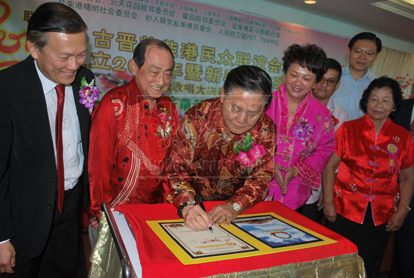 LEAVING A MARK: Yong appends his signature on a special publication of Sungai Maong Community Association as (from left) Giam, Sim, Chai and other guests look on. The book is published in conjunction with the association's 20th anniversary.