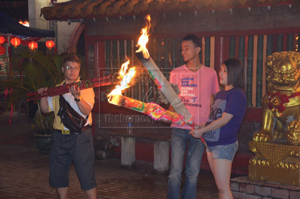 CARRYING ON TRADITION: A group of youths burn joss sticks.