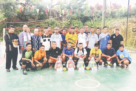 BERPELUANG: Paruwadi (berdiri lima kanan), Abdul Rahman (tiga kanan) dan Azman (dua kiri) bersama para pemain pada kejohanan sepak takraw di Kampung Semerah Padi, Kuching Ahad lalu.