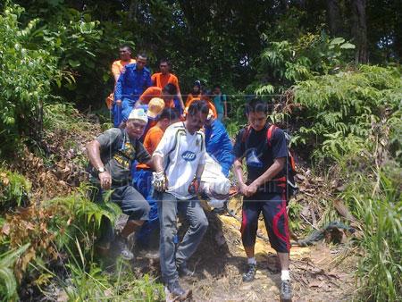 MENINGGAL DUNIA: Beberapa anggota JPAM yang turut dibantu oleh rakan-rakan mangsa membawa keluar mayat dari gunung tersebut.