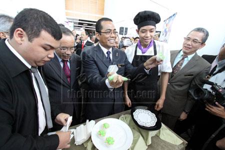 SIAP: Khaled menunjukkan kek cawan yang dihiasnya semasa melawat tapak pameran yang diadakan sempena majlis pelancaran Pemerkasaan Kolej Komuniti di BCCK, semalam. Turut kelihatan Fadillah (kanan).