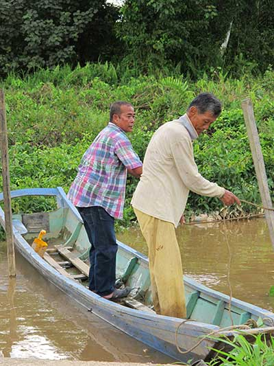 OLD BUDDIES: Two good friends in a boat – Abdillah (left) lending a hand to Mr Ling who is related to pioneer Ling Ching Tu.