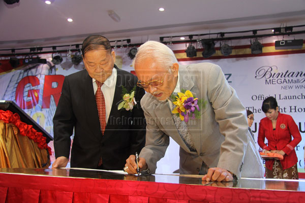 FOR THE RECORD: Taib signing a plaque to commemorate the simultaneous opening of Meritz Hotel, Parkson, GSC and Bintang Megamall New Wing.