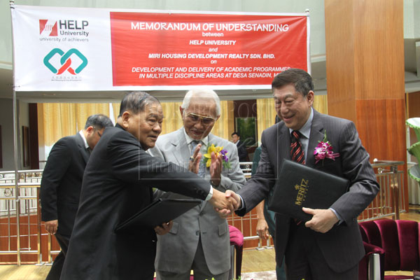 TOWARDS BETTER COLLABORATION: Lau (left) exchanging signed MoU with Paul Chan of HELP University, witnessed by Taib (centre).