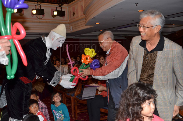 NICE: Talib (second right) receiving flowers made from balloons from a clown. At right is Wahap.
