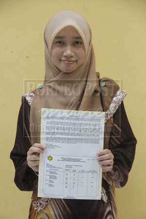 FLYING COLOURS: Best student Noraini showing off her STPM examination results.