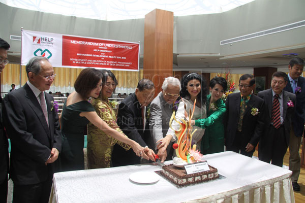 1ST ANNIVERSARY: Taib (fifth left) cutting the anniversary cake of Meritz Hotel at its opening ceremony.