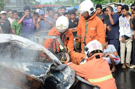 PIHAK bomba mengeluarkan mayat mangsa yang terperangkap di dalam kenderaannya.