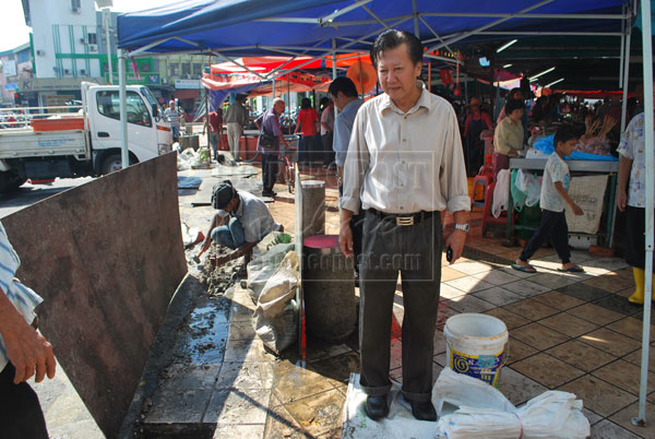 INSPECTION: Chieng checks on the progress to build a drain near 'tamu' market to prevent water spilling onto the main road.