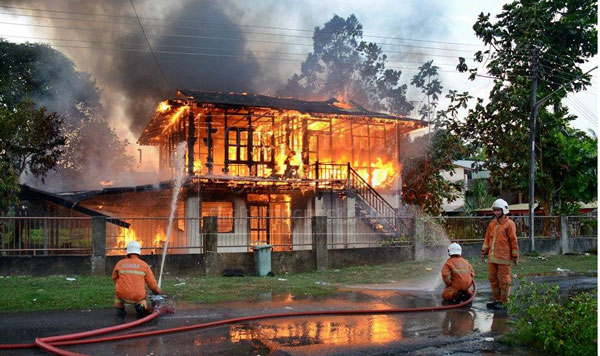 THE BLAZE AT ITS HEIGHT: Fire-fighters dousing the fire.