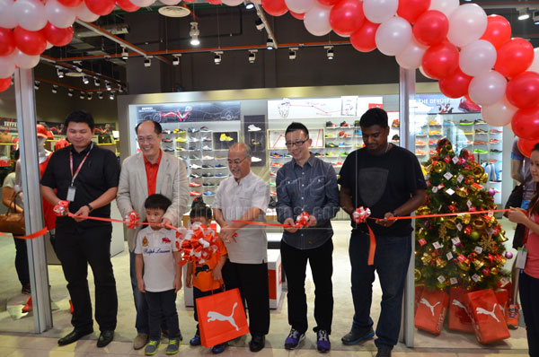 PUMA IN TOWN  Patrick (centre) cutting the ribbon to mark the official  opening of the new Puma outlet at Cityone Mall. With him are Raymond  (second left) d18dee540ba3
