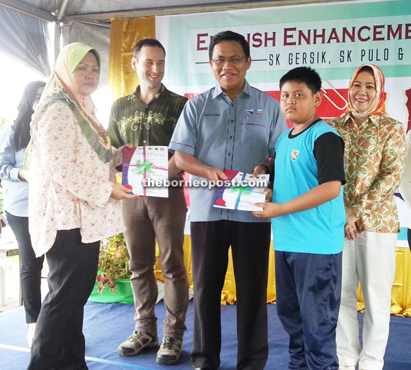 Dr Abdul Rahman (centre) presenting certificates of participation as others look on.