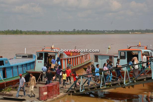 People disembarking at Sibu Wharf near the Tua Pek Kong Temple.