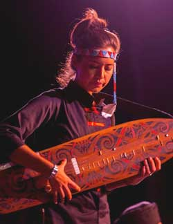 Alena  playing  the sape' during  a show.