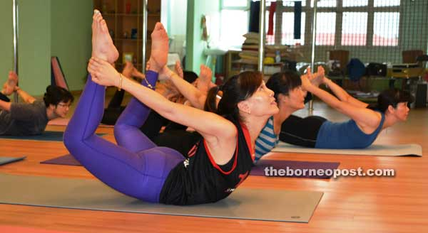Kong leads students with the bow pose, which is said to relieve back pain.