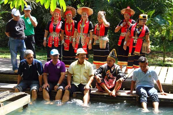 Tourism Ministry permanent secretary Ik Pahon Joyik (centre) dips his feet in the warm water.