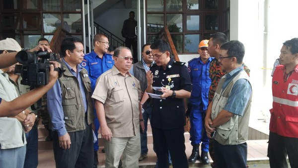 Deputy Chief Minister Tan Sri Pairiung Kitingan being briefed on the latest development by Ranau OCPD DSP Farhan Lee Abdullah at the operation room in Kinabalu Park.