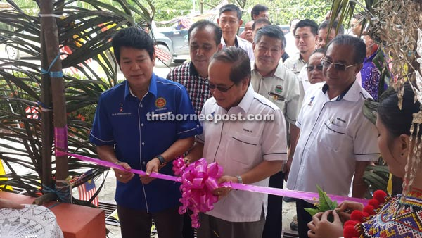 Uggah cutting the ribbon to officiate at the programme, witnessed by Rayong (left) and other officials.