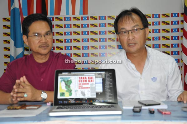 Baru (right) showing the map of the affected areas and their rallying cry in defending their lands during the press conference. On the left is state PKR deputy chairman Abang Zulkifli Abang Engkeh.