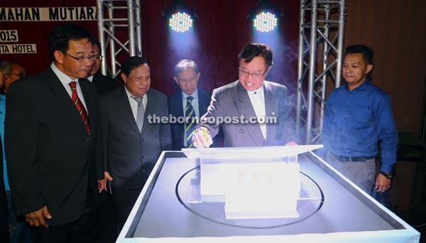 Abang Johari (second right) appends his signature on the logo of Mutiara Mortgage & Credit Sdn Bhd. — Photo by Muhamad Rais Sanusi