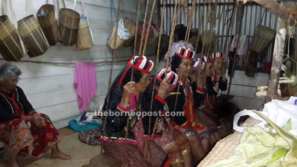 Female shamans reciting prayers to their deities at the village's 'Boli Gawea' while sitting on a swing.