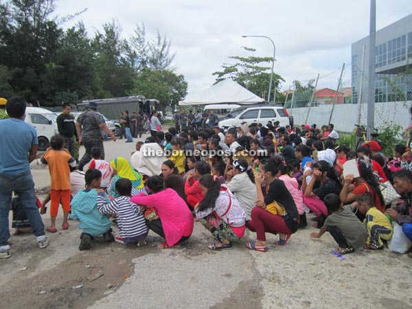 A section of the illegal immigrants wait at the PWD jetty in Piasau Industrial Estate before they board the boat to take them out to the sea.